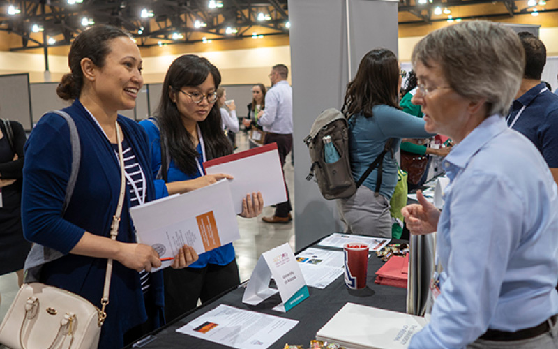 Photo of exhibitor interacting with two attendees